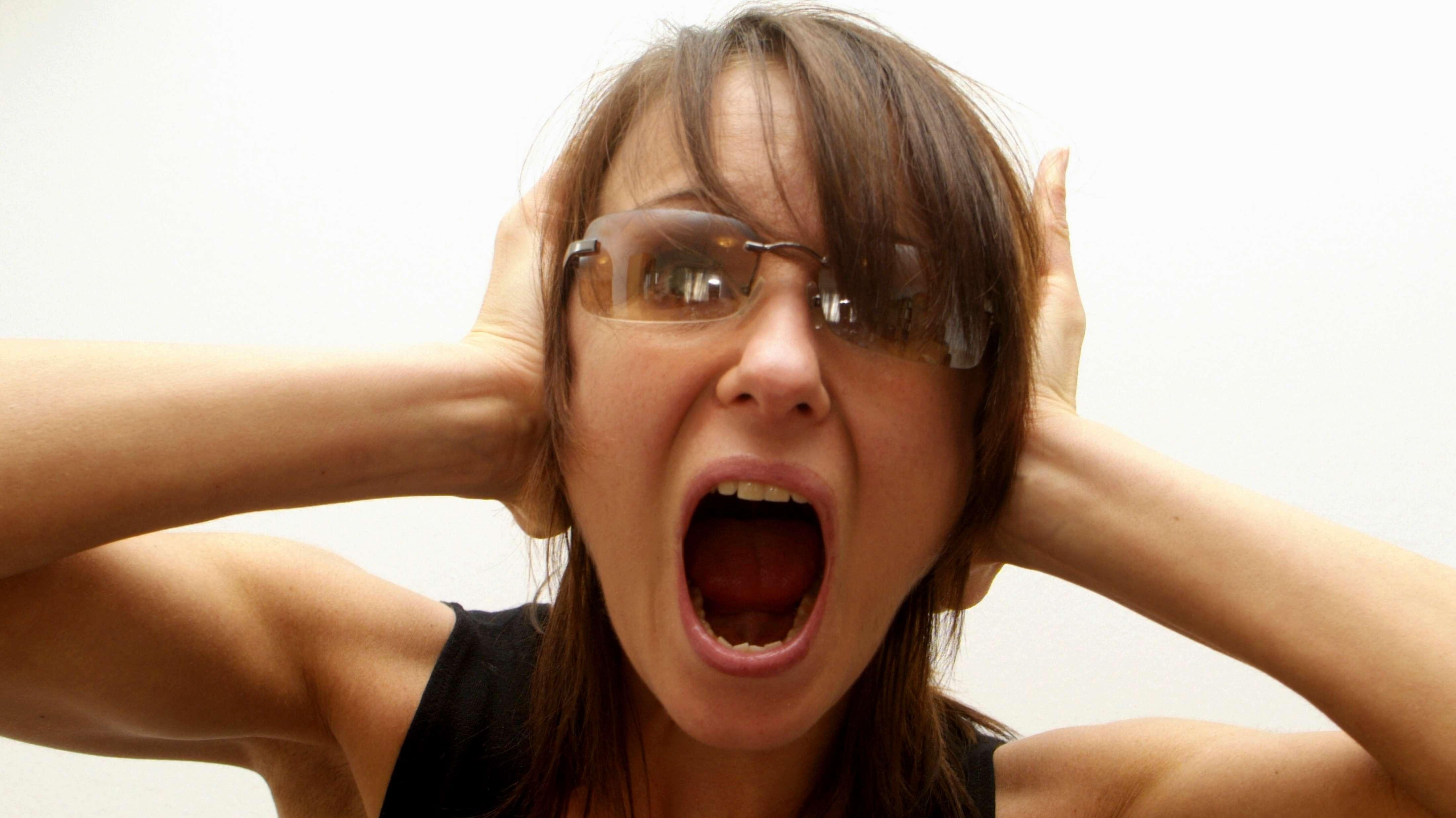 Schreiende Frau hält sich die Ohren zu