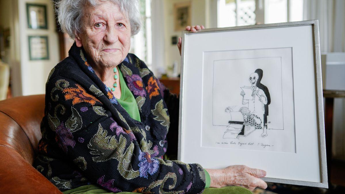 Ingrid Noll zeigt, im Sessel sitzend, eine gerahmte Zeichnung von Tomi Ungerer, auf der sie schreibend zu sehen ist, hinter ihr Gevatter Tod