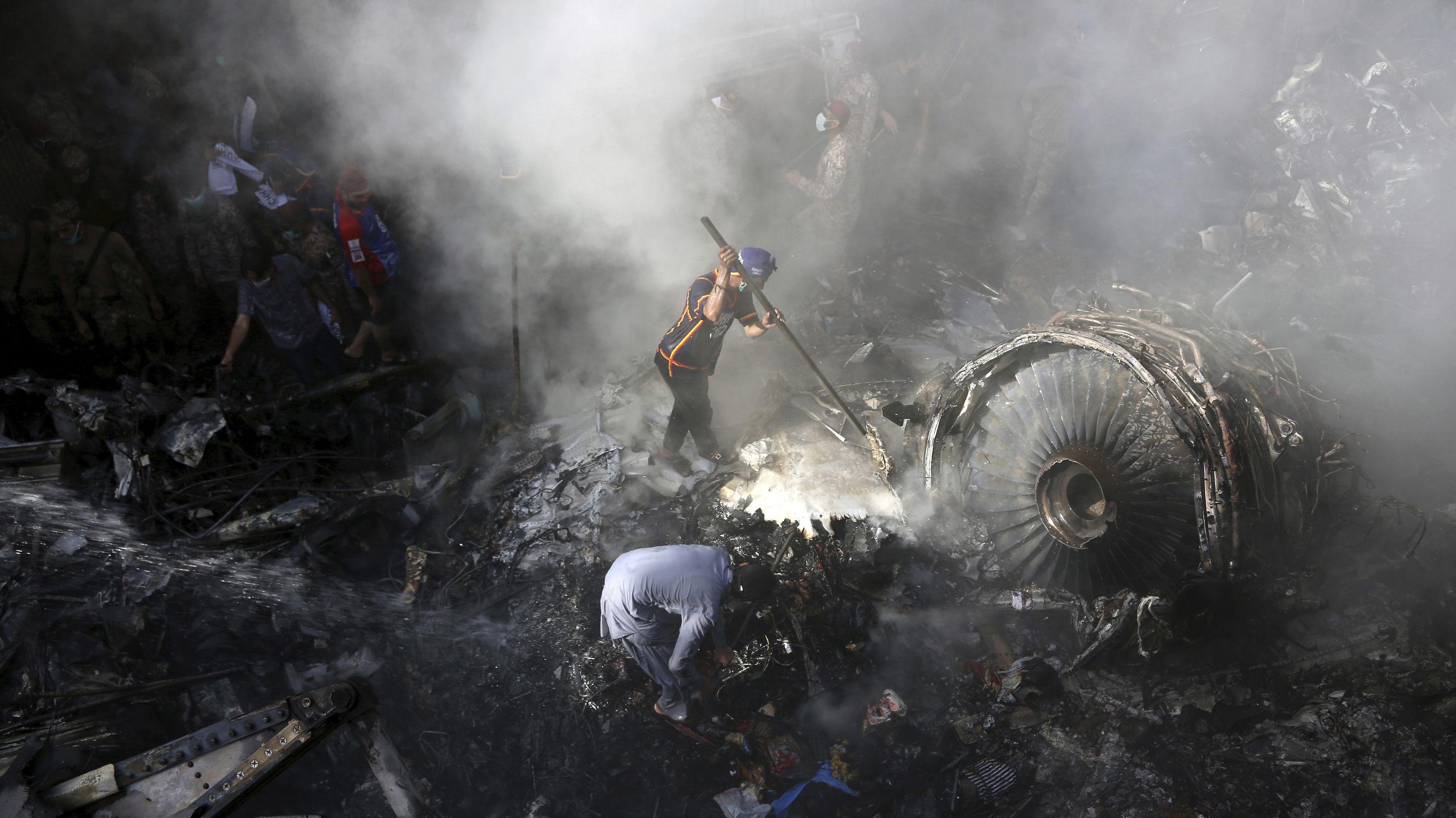 Ein Mann mit einer Schaufel sucht gemeinsam mit anderen nach Menschen neben einer Turbine.