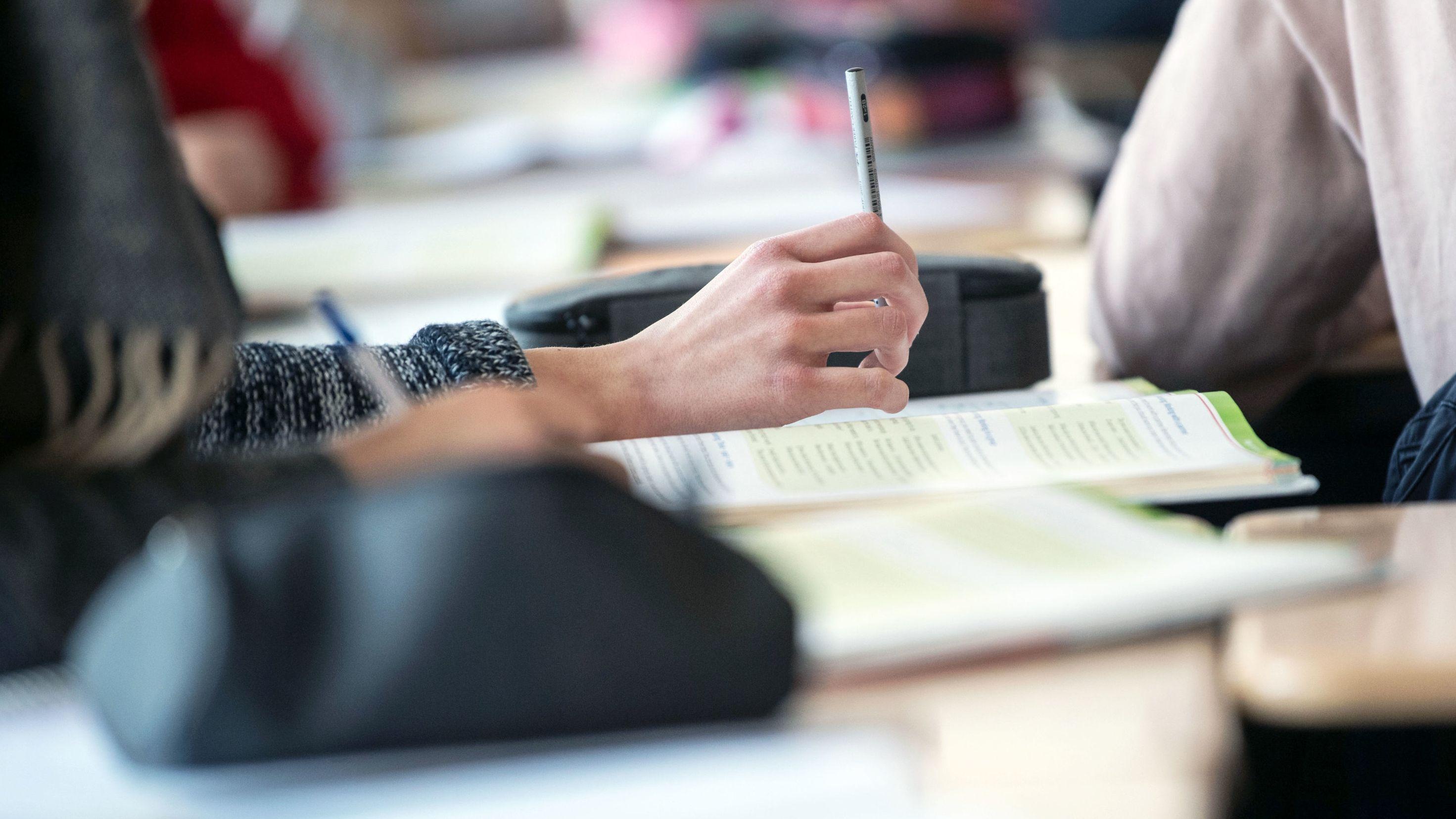 Ein geöffnetes Schulbuch liegt auf einem Tisch.