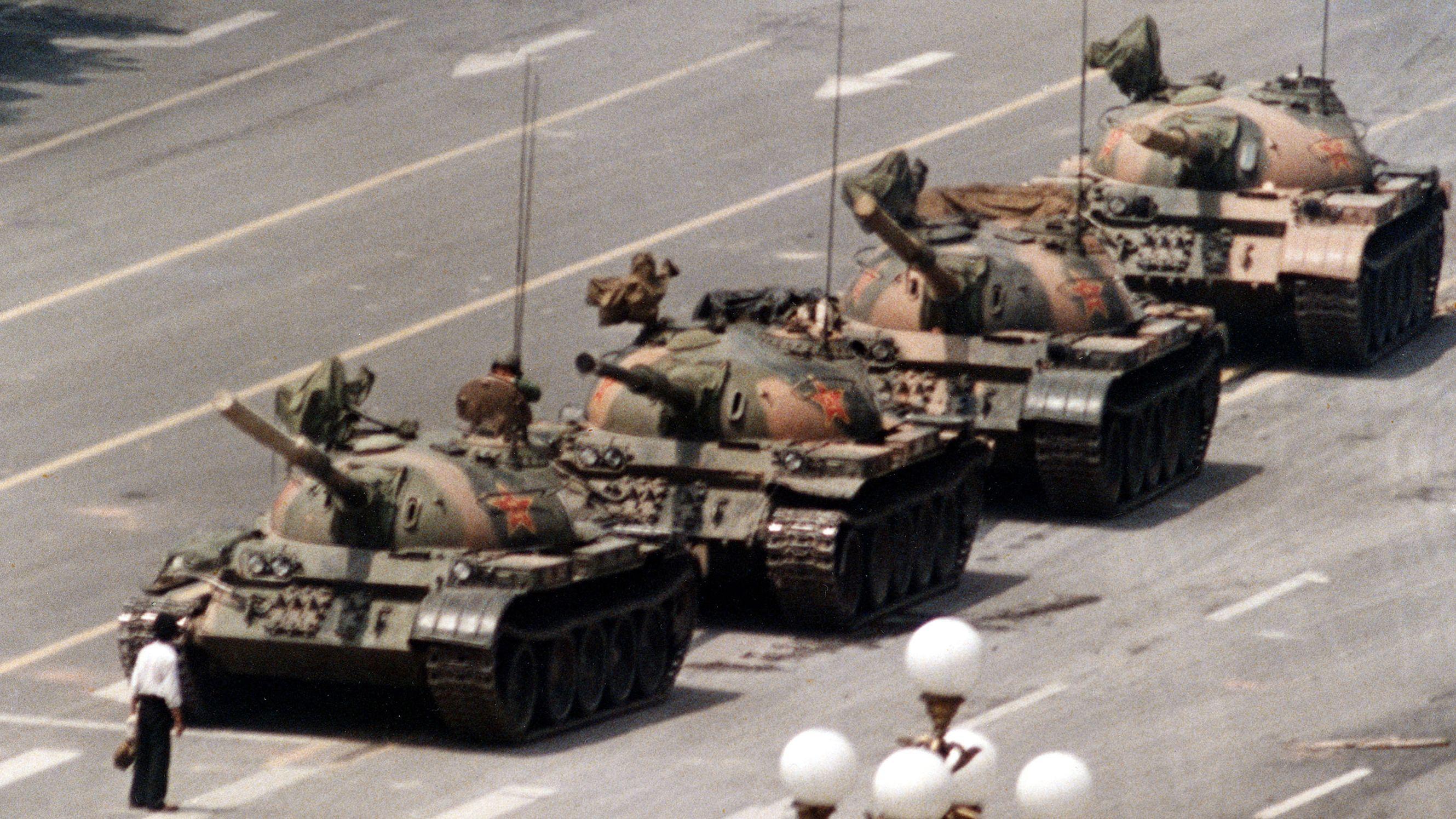 Ein Mann im weißen Hemd steht vor vier Panzern.