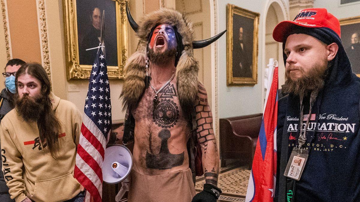 """Jacob C. (Bildmitte)  sorgte bei der Erstürmung des US-Kapitols als """"Hörner-Mann für Schlagzeilen."""""""