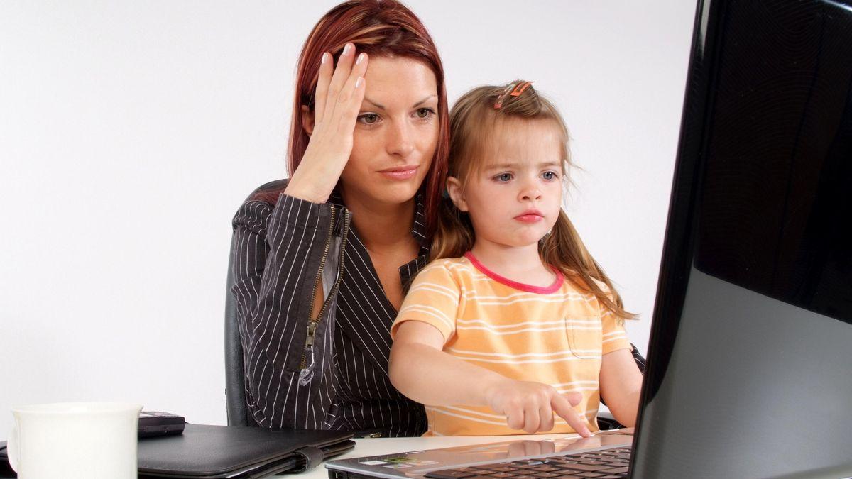 Frau mit Kind vor Laptop.