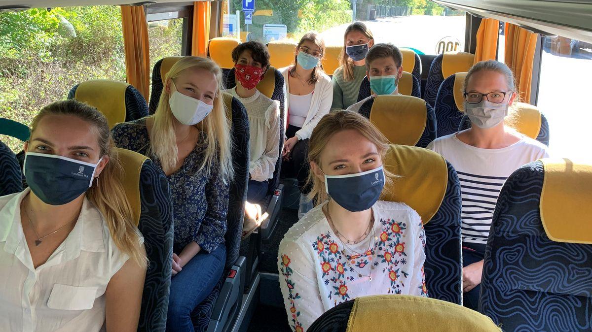 Acht  Studierende sitzen auf blauen Sitzen im Inneren eines Kleinbuses. Sie tragen alle einen Mund-Nase-Schutz.