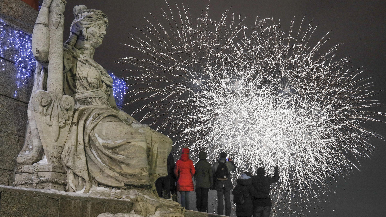 Feiernde Menschen in St. Petersburg bewundern das Lichtspektakel am Himmel.