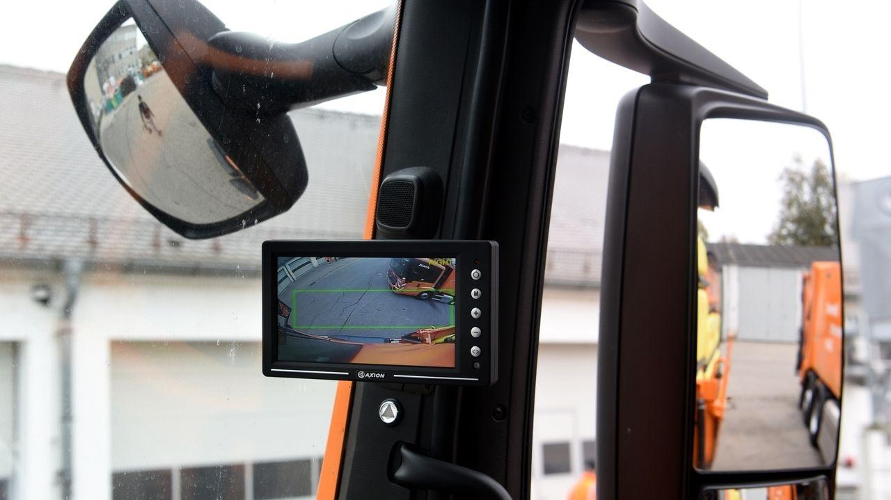 Blick nach rechts aus dem Fenster eines städtischen Lkw mit Abbiege-Assistenten: Ein Monitor und zwei Außenspiegel