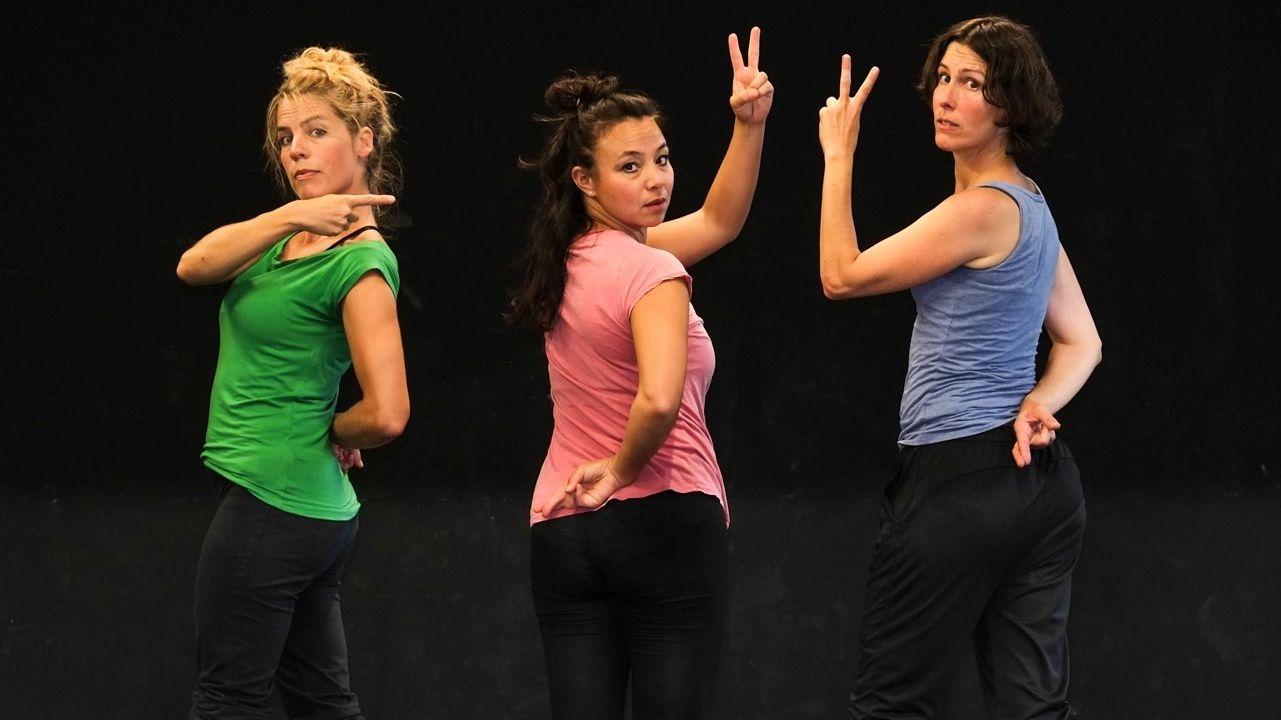 """""""Ich war das nicht"""" von Sabine Karb: Drei Frauen in unterschiedlich farbigen T-Shirts in Rückenansicht blicken über die Schulter in die Kamera"""