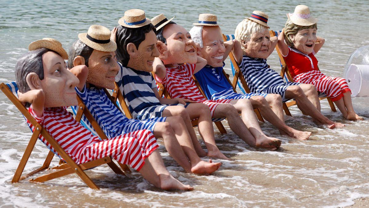Oxfam-Aktivisten sitzen in gestreiften Badeanzügen auf Liegestühlen am Strand und tragen aus Papiermaschee die Köpfe von G7-Spitzenpolitikern und drücken damit ihren Protest aus.
