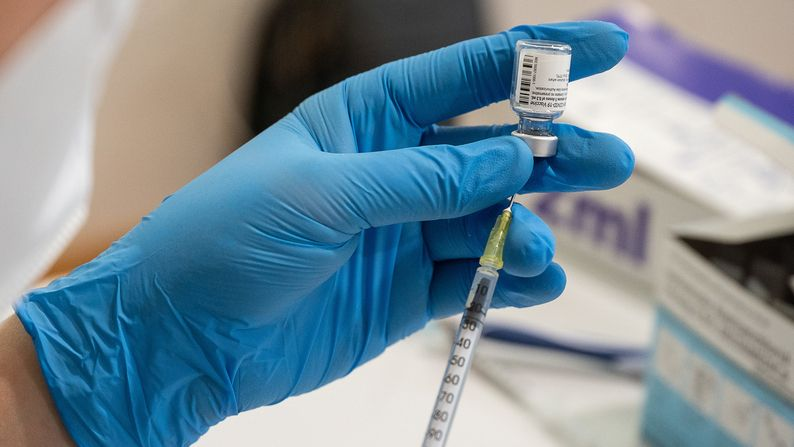 Die Mitarbeiterin eines mobilen Impfteams zieht Impfstoff in eine Spritze auf.