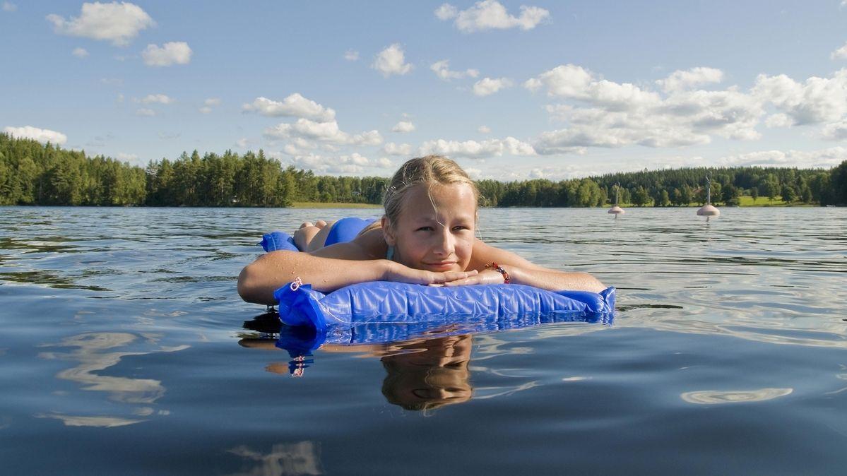 Mädchen treibt mit Lufmatratze auf einem See.