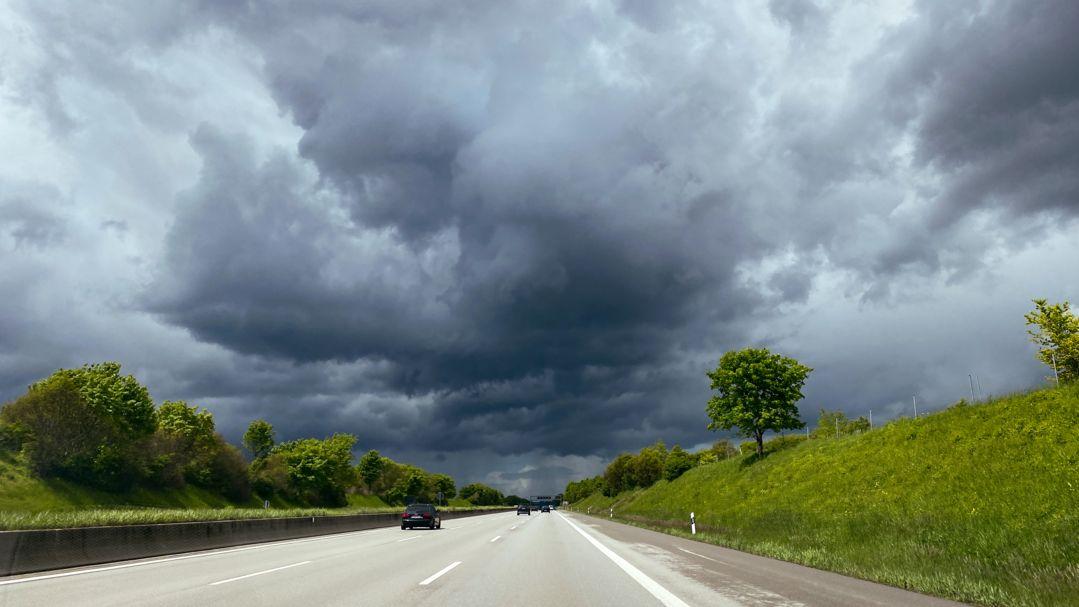 Dunkle Wolken am Himmel über einer Autobahn.