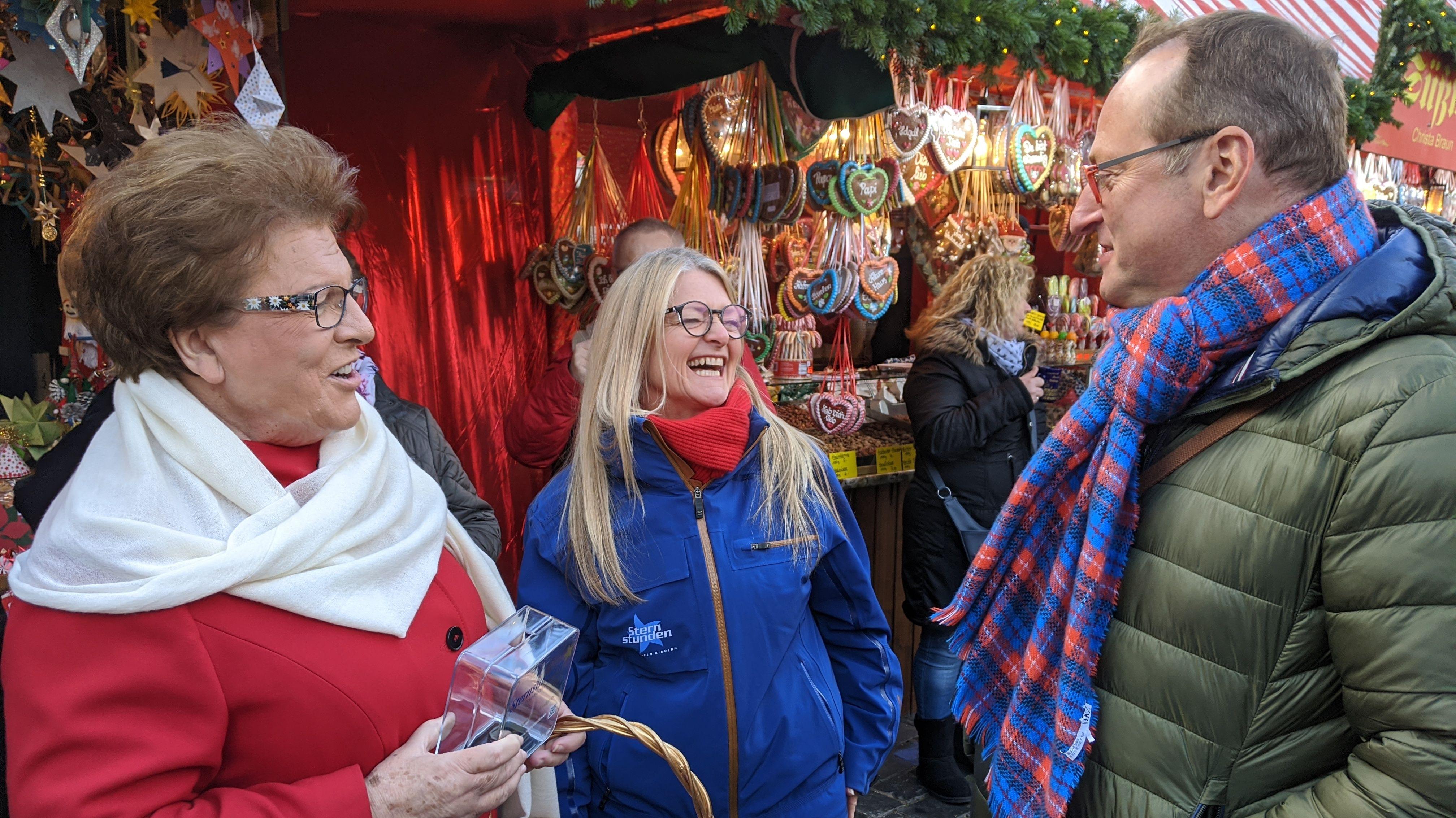 Barbara Stamm und Volker Heißmann lachend vor einem Stand mit Lebkuchenherzen