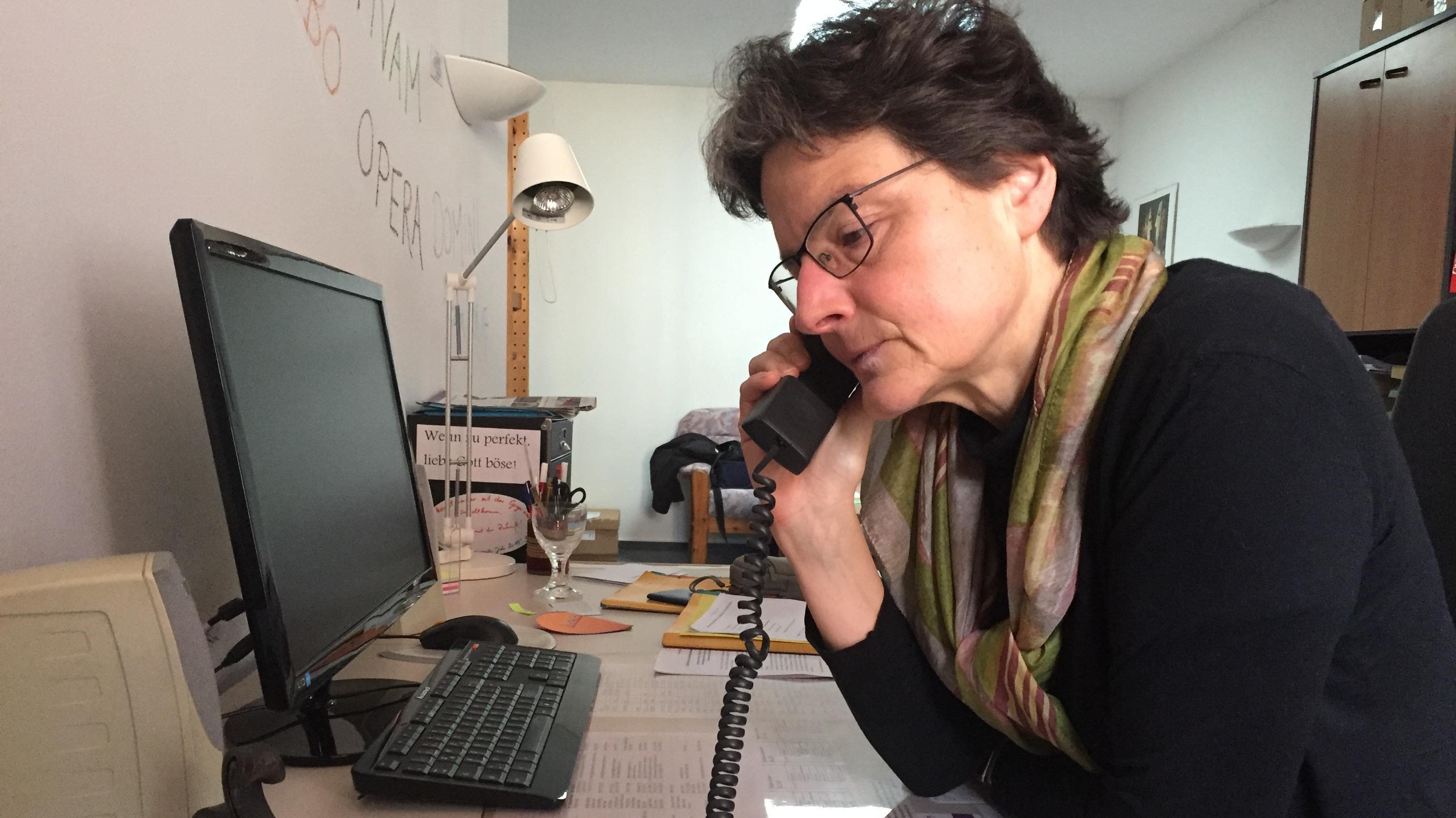 Frau mit einem Telefonhörer in der Hand