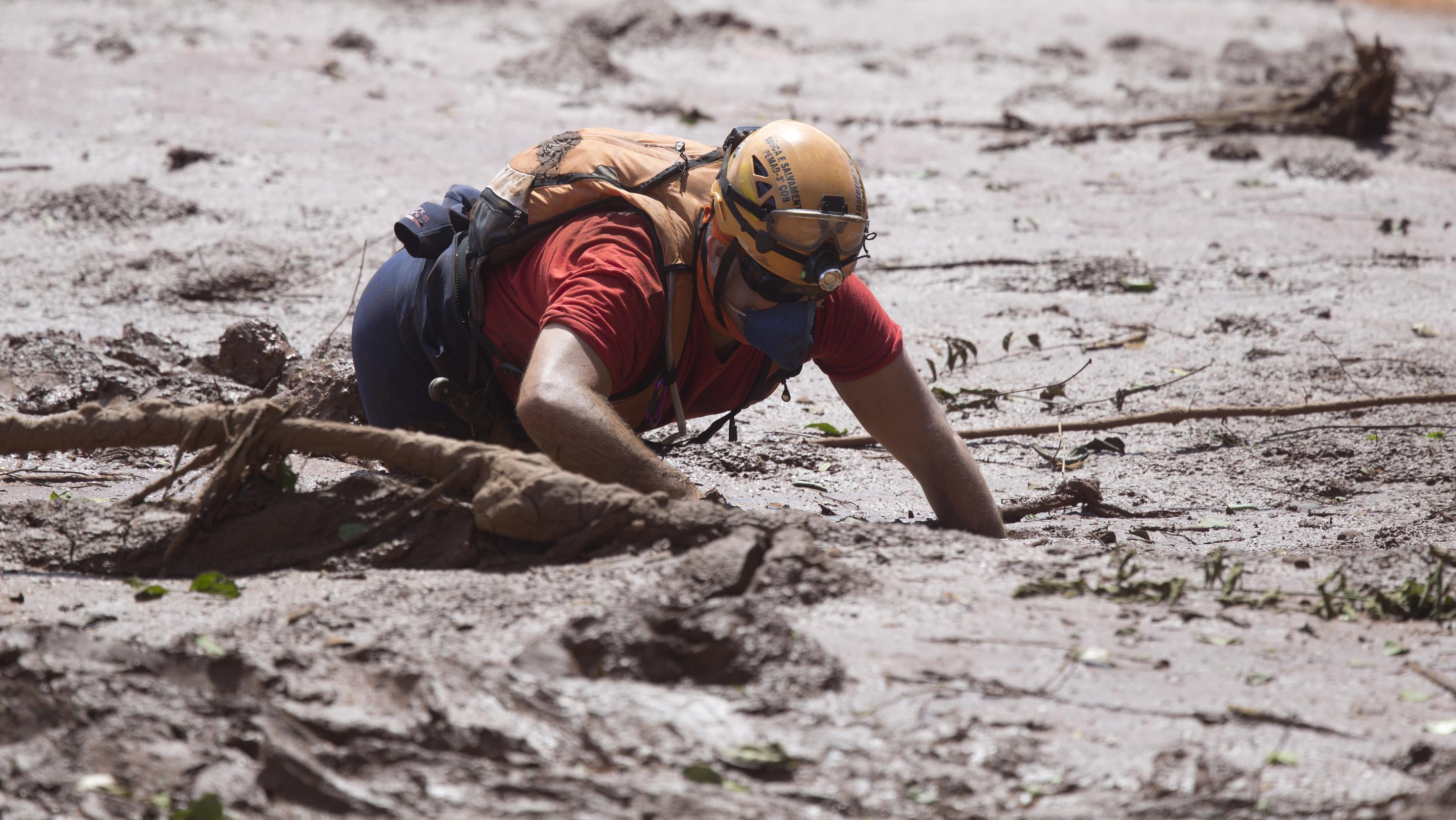 Brasilien, Brumadinho: EinRettungshelfer arbeitet im Schlamm auf der Suche nach möglichen Opfer des Dammbruchs.