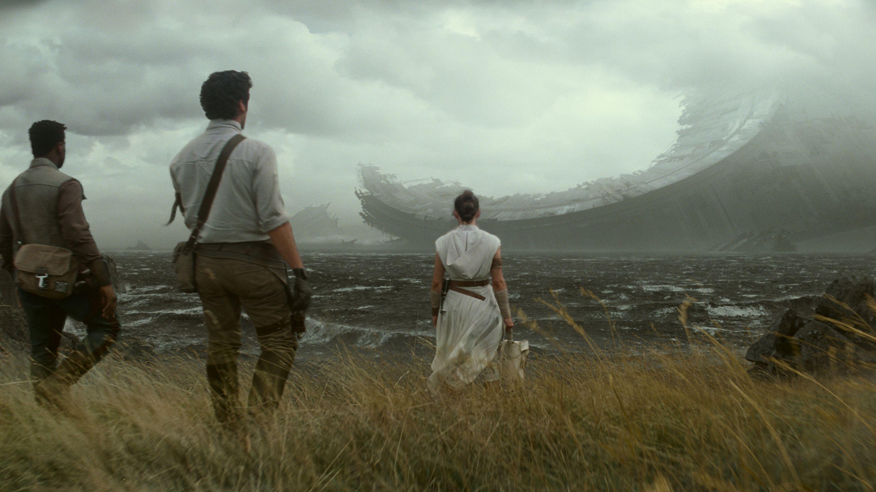 """Filmszene aus """"Star Wars 9"""": Eine Frau und zwei Männer stehen, mit dem Rücken zur Kamera vor einer Meeresbucht mit einer riesigen Raumschiff-Ruine"""