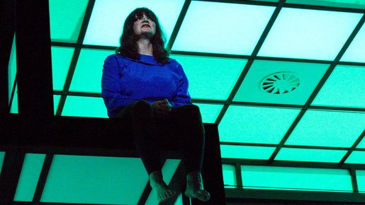 Eine Schauspielerin sitzt auf der Kante einer raumartigen Kulisse.