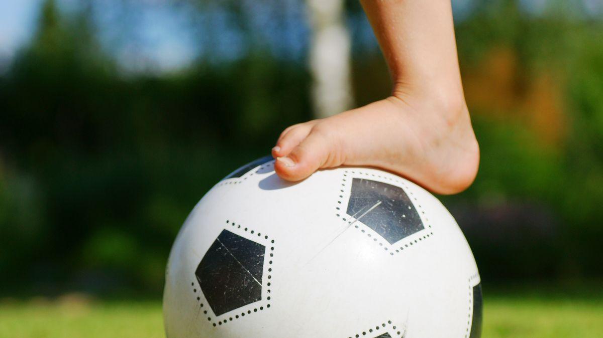 Nackter Kinderfuß auf einem Fussball