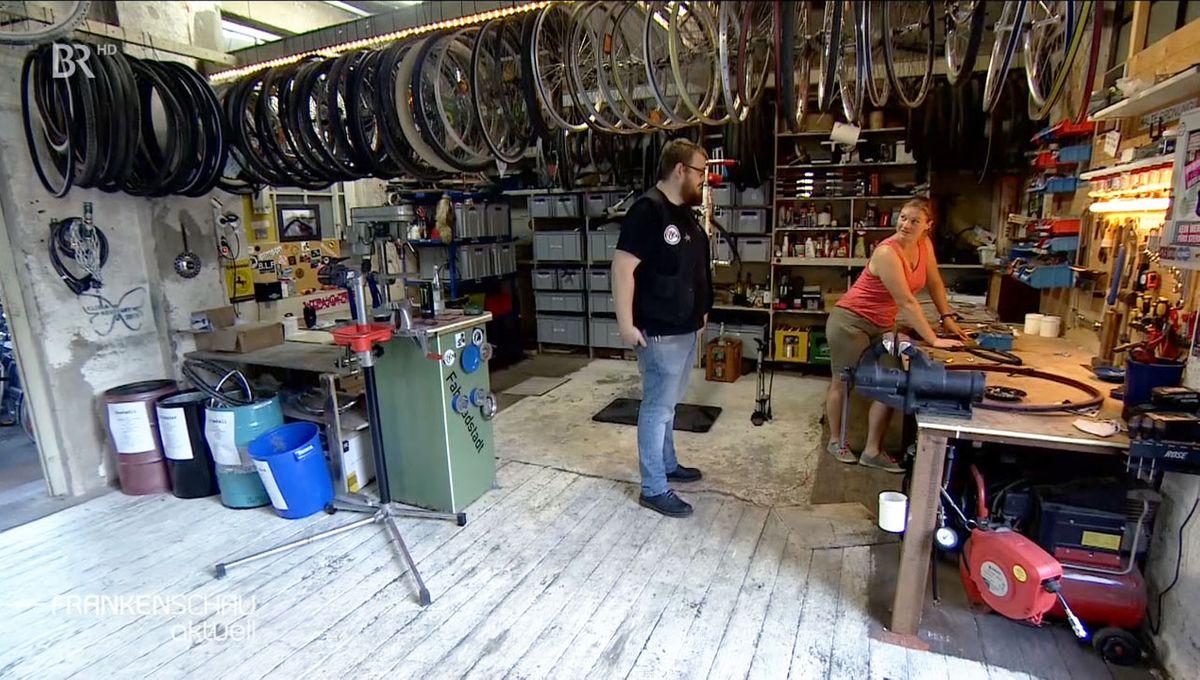 Ein Mann und eine Frau unterhalten sich in einer Fahrradwerkstatt.