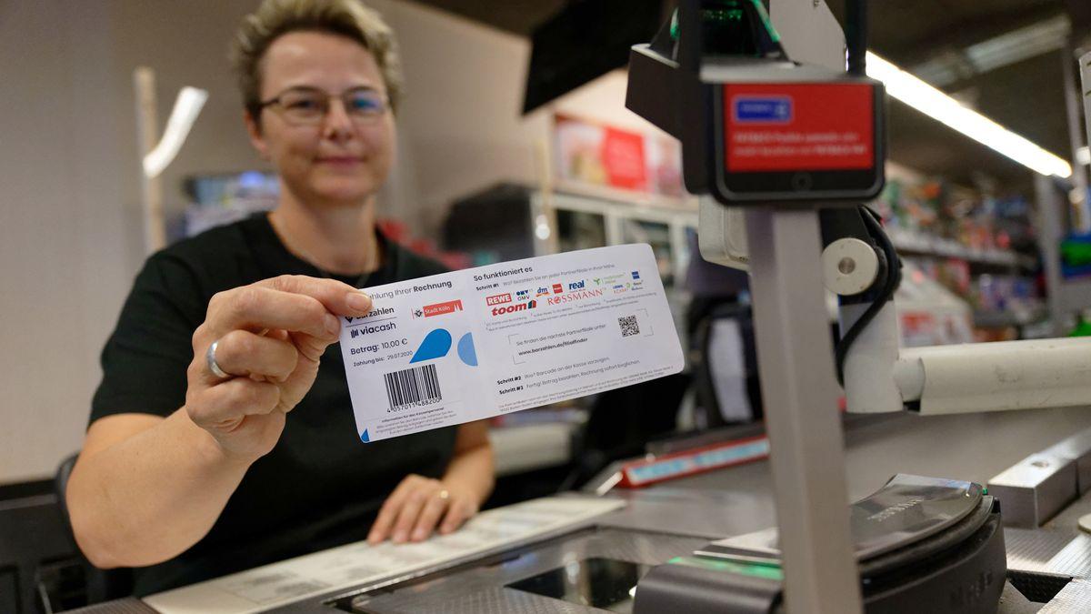 Eine Mitarbeiterin in einer Filiale des Einzelhändlers REWE hält ein Blatt mit einem Barcode in der Hand