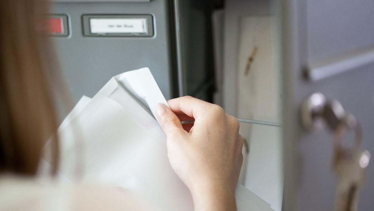 Frau holt Post aus ihrem Briefkasten.