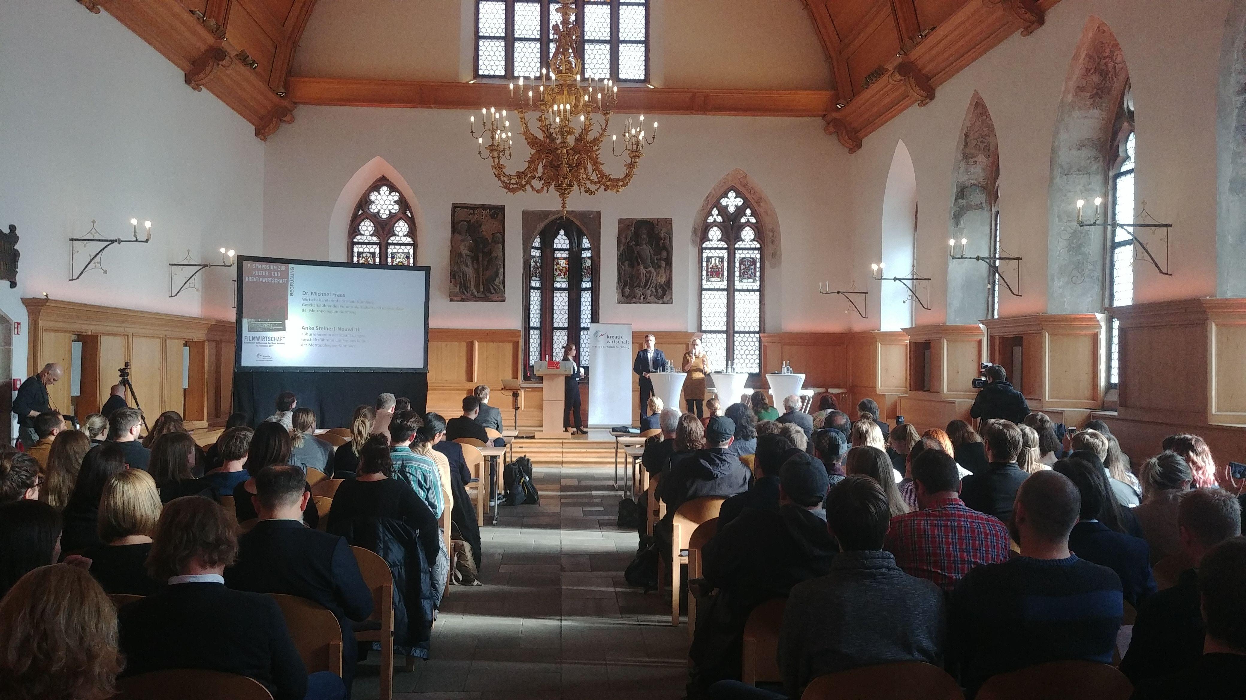 Menschen bei einem Vortrag im historischen Rathaussaal in Nürnberg