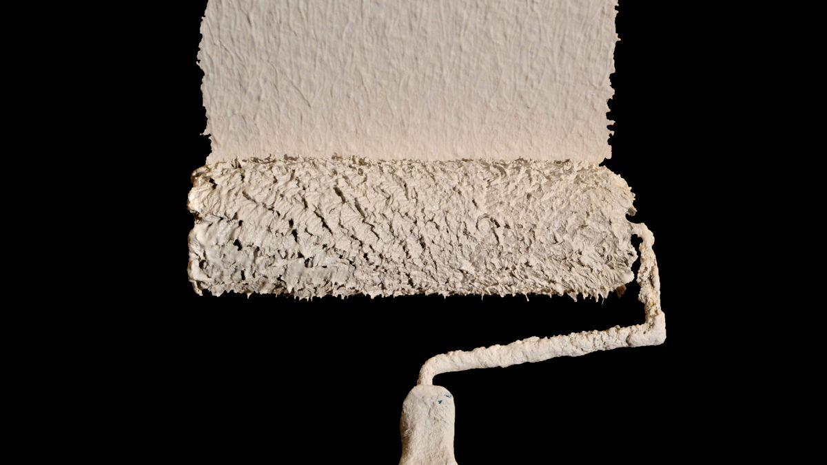 Malerrolle malt weiße Farbe an schwarze Wand