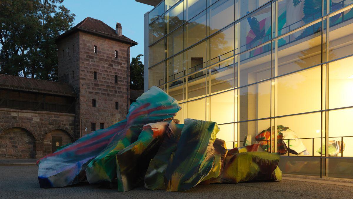 Auf einem Platz umgeben von der Burgmauer liegt eine bunte Skulptur im Abendlicht vor dem Neuen Museum in Nürnberg, das von innen beleuchtet ist.