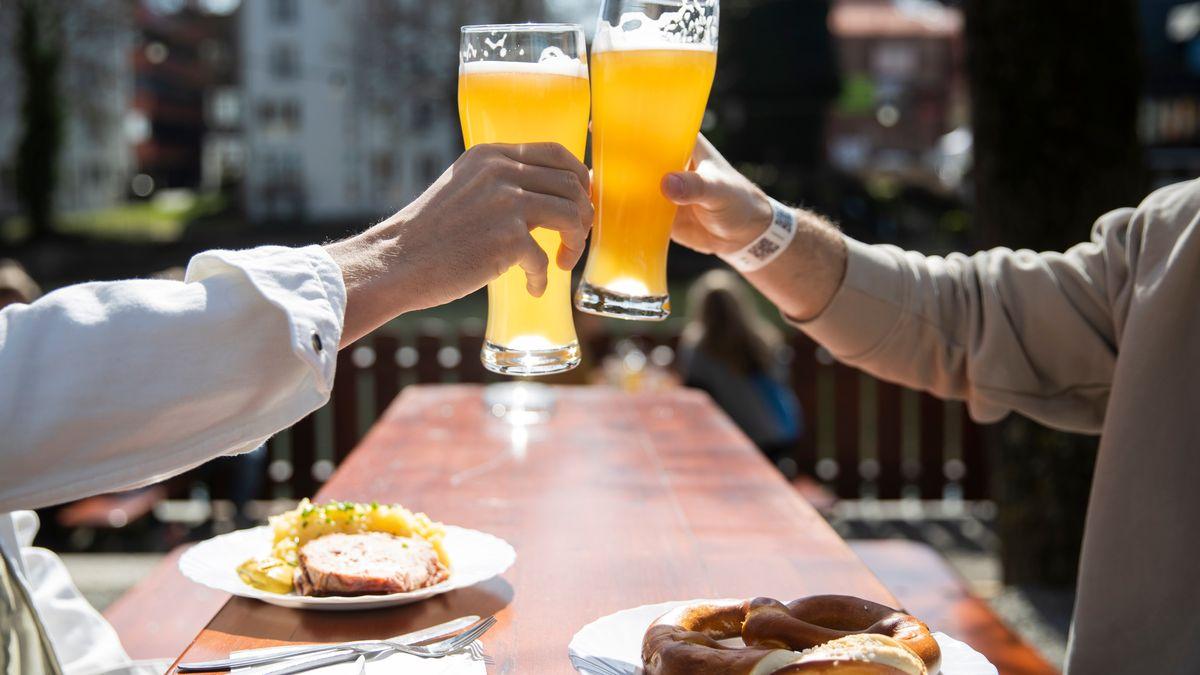 Zwei Menschen sitzen bei gutem Wetter in einem Biergarten und stoßen mit einem Bier an.