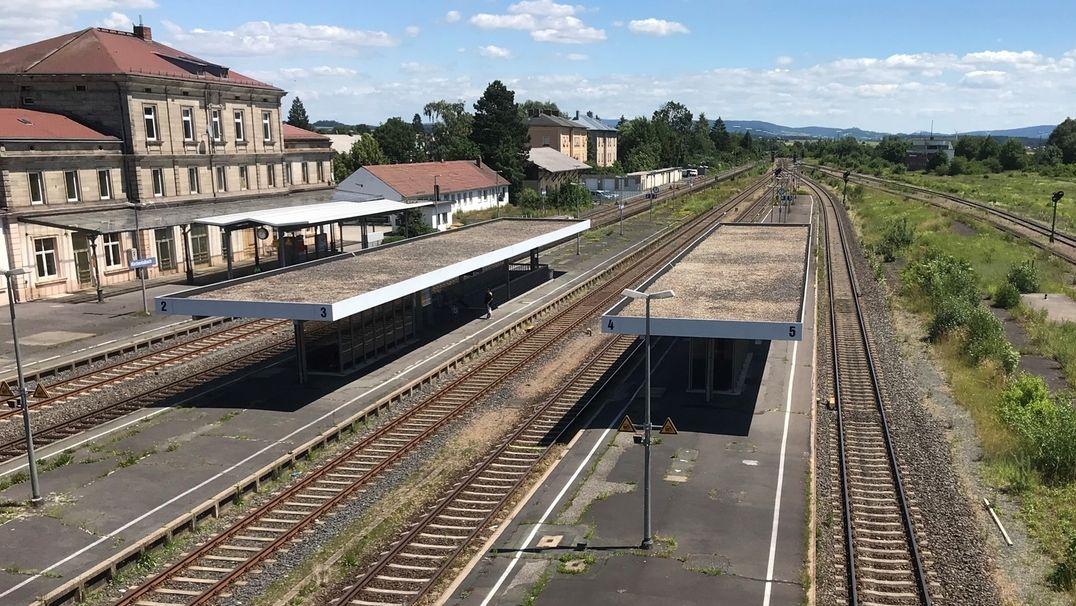Das Bahnhofsgebäude von Kirchenlaibach, davor mehrere Gleise, die zum Teil überdacht sind, aus der Vogelperspektive betrachtet.