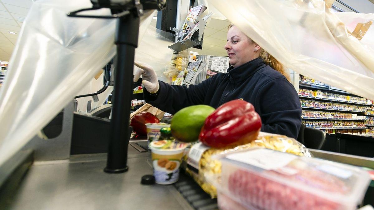 Kassiererin unter einer Plastikplane schützt sich vor Corona.
