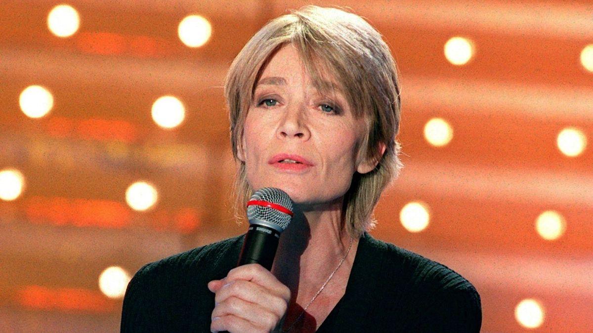 Die Sängerin mit Mikrofon vor orangem Hintergrund