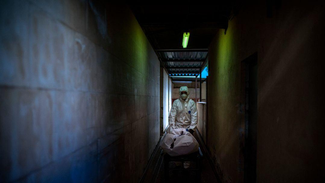 Ein Mitarbeiter der Leichenhalle eines Krankenhauses transportiert den Leichnam eines Covid-19-Opfers auf einer Bahre.