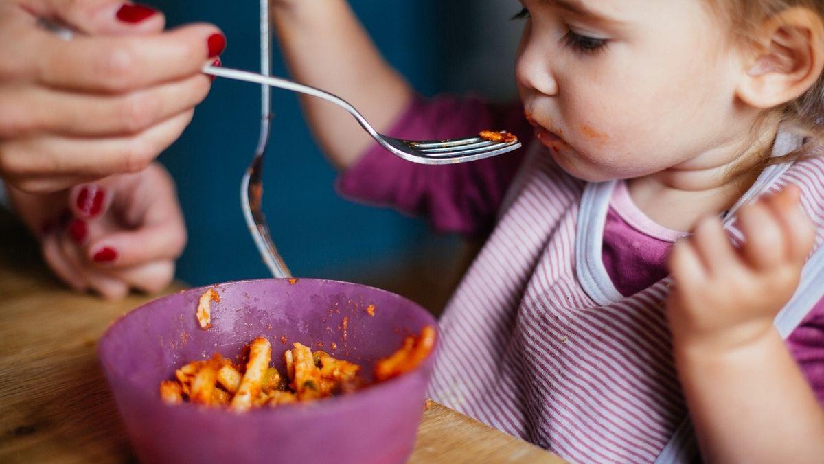 Kleinkind wird von einer Frau mit Nudeln gefüttert.