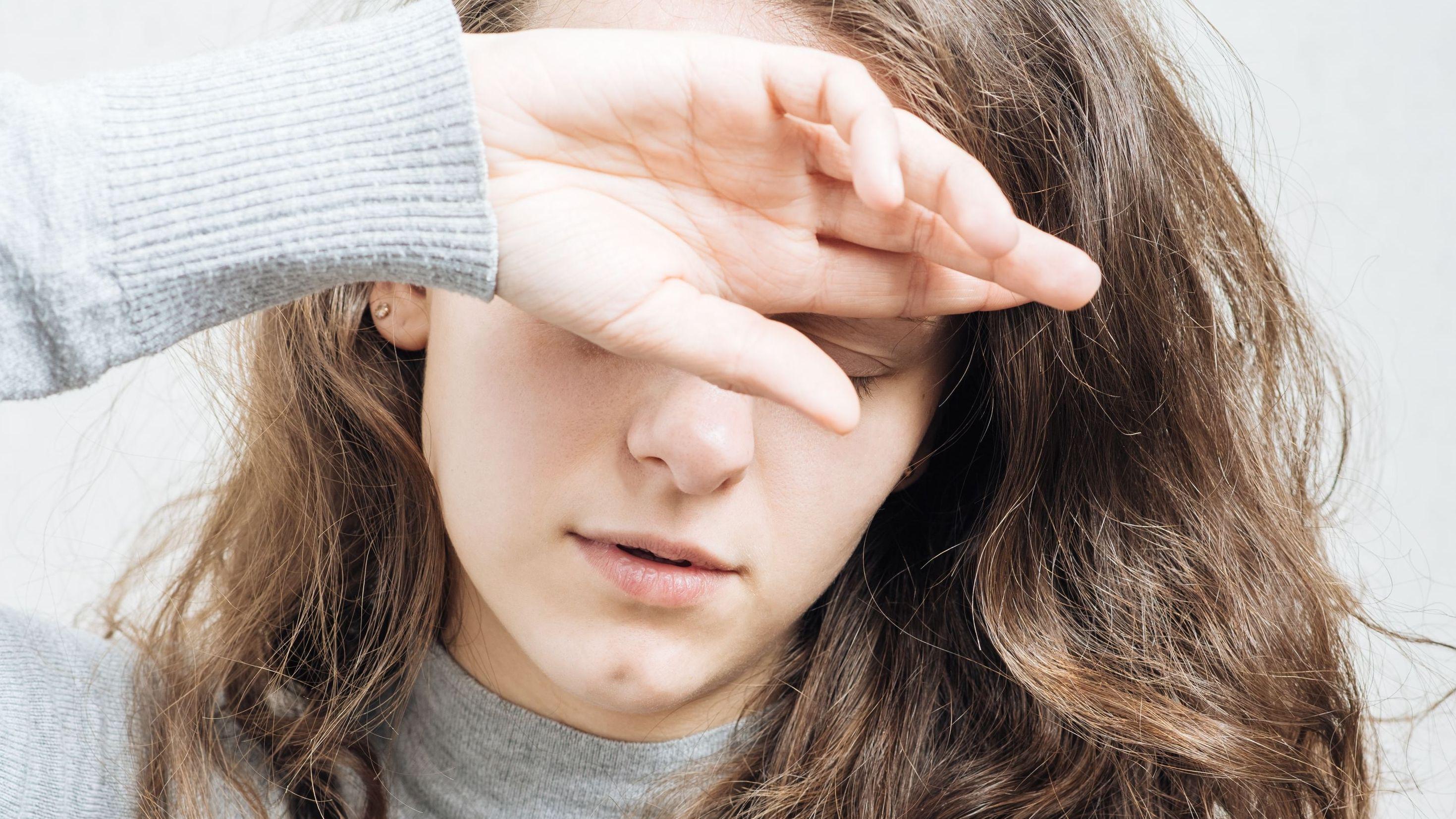 Symbolbild: ME/CFS (Mylagische Enzephalomyelitis), auch bekannt als Chronisches Erschöpfungssyndrom. Eine Frau hält ihren Kopf in den Händen.
