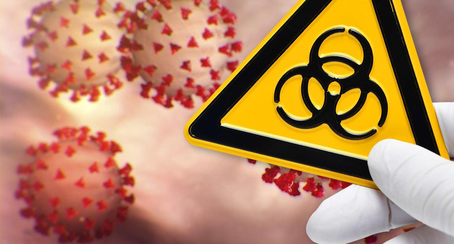 Im Hintergrund eine schematische Darstellung von Coronaviren, im Vordergrund eine behandschuhte Hand, die ein Schild für biologische Gefährdung hochhält.