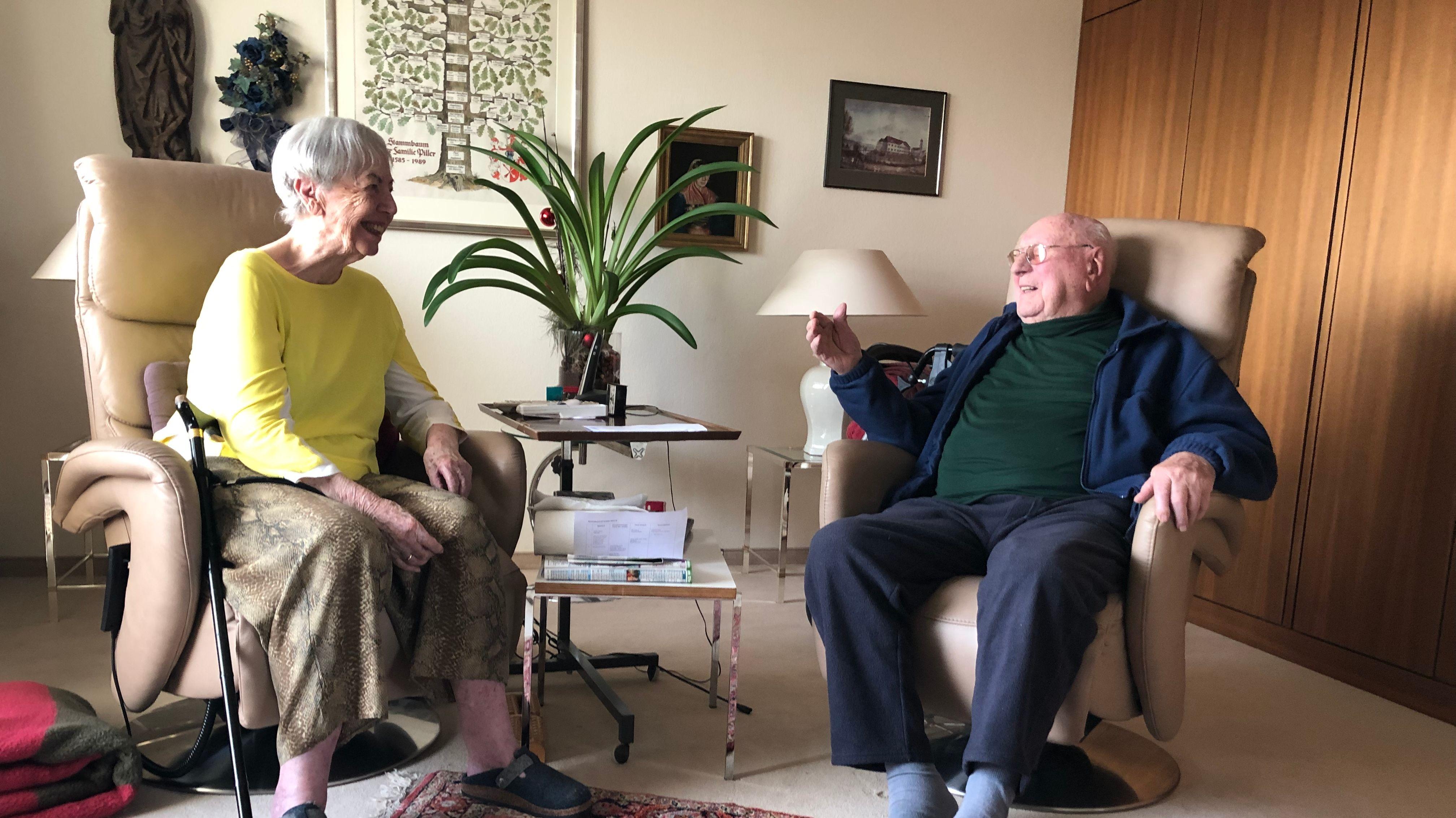 Frau und Herr Piller sitzen auf Sesseln in ihrem Wohnzimmer