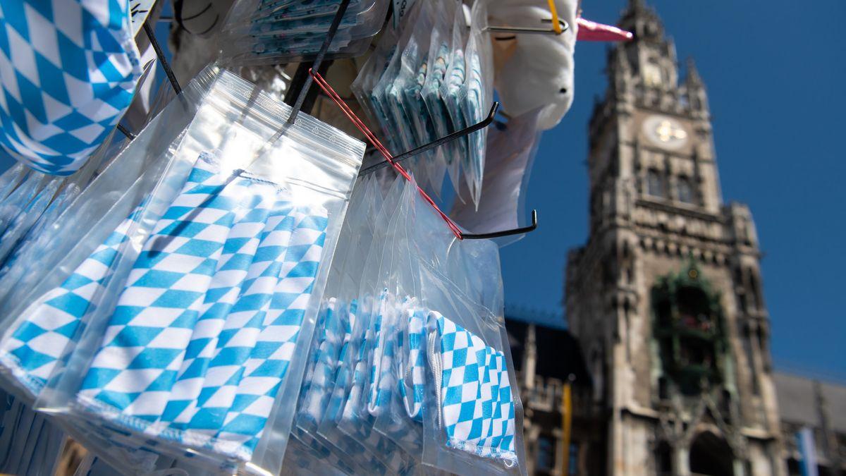 München: Ein Souvenirstand auf dem Marienplatz bietet Mundschutze mit der bayerischen Rautenflagge an.