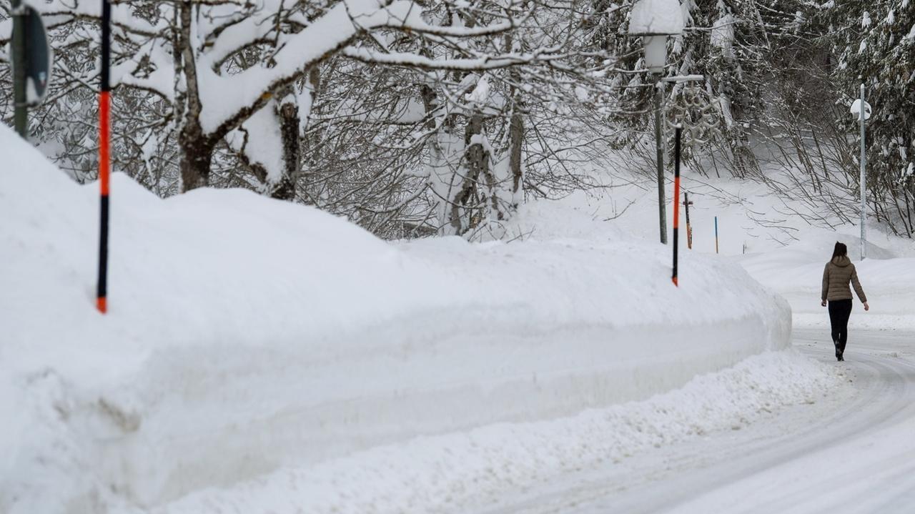 Eine zugeschneite Straße am Alpenrand, am Straßenran türmt sich der geräumte Schnee rund 2 Meter hoch