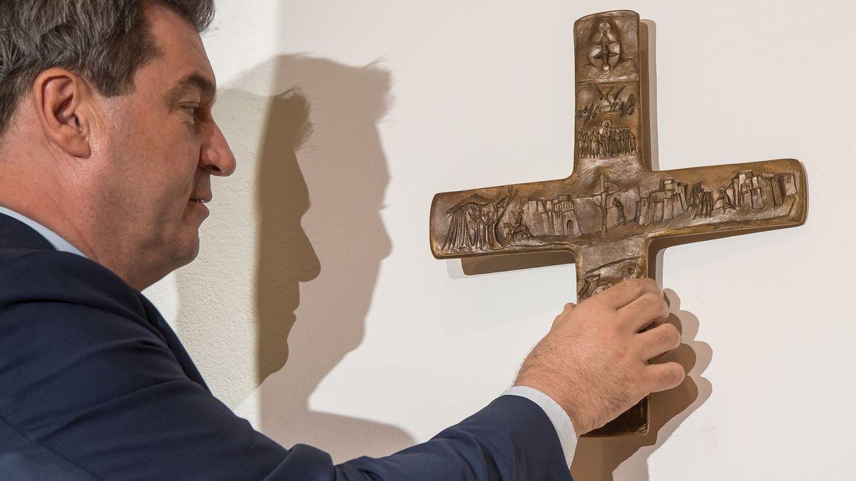 Markus Söder hängt ein Kreuz auf