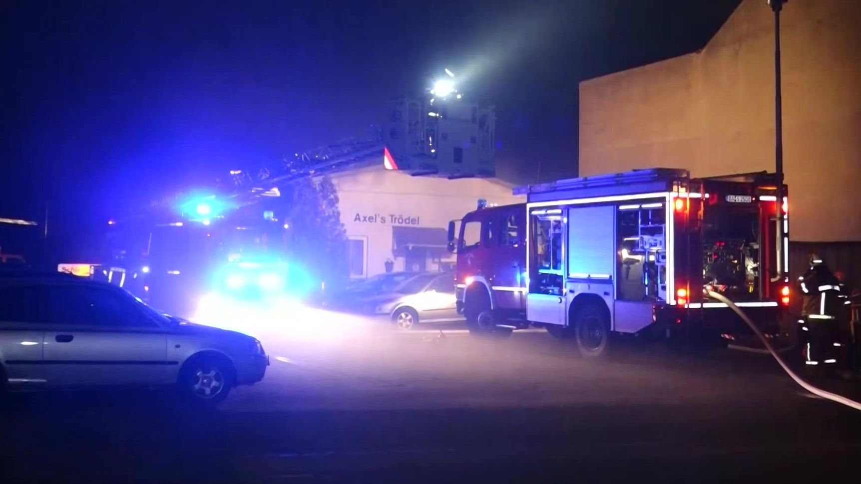 Zwei Feuerwehrautos stehen vor der Werkshalle, in dem ein Feuer ausgebrochen war.