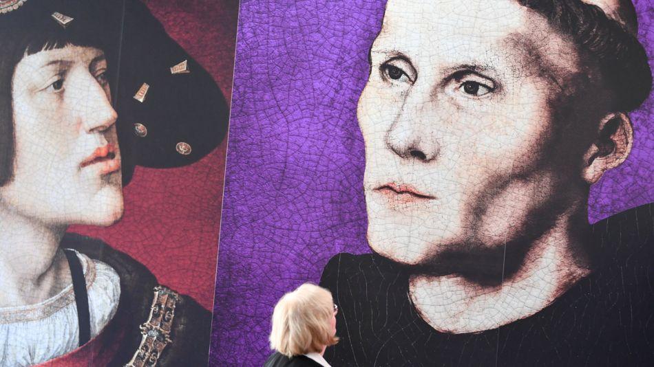 """ARCHIV - 13.02.2017, Rheinland-Pfalz, Worms: Eine Frau steht in der Ausstellung """"Luther in Worms 1521 - Der Ort des Geschehens"""" vor Bildern von Martin Luther (r) und König Karl dem Fünften."""