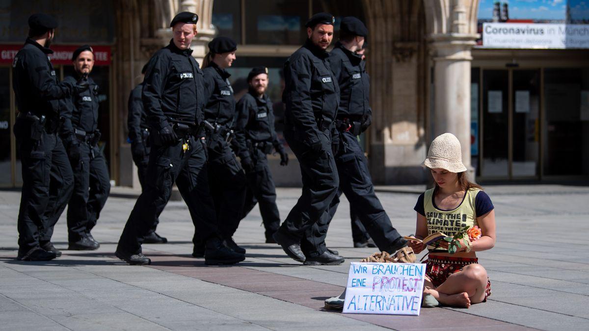 """Eine Teilnehmerin der Kundgebung """"Lesen für die Demokratie"""" sitzt auf dem Marienplatz und hat dabei ein Schild mit der Aufschrift """"Wir brauchen eine Protest Alternative"""" aufgestellt. Dahinter geht eine Gruppe Polizisten entlang."""
