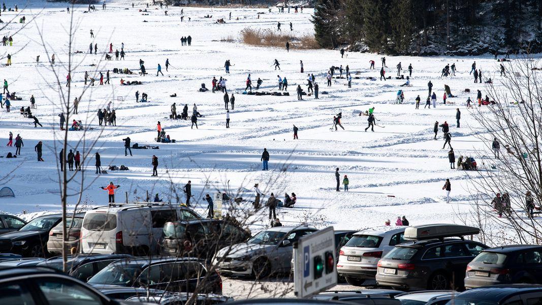Parkende Autos von Tagesausflüglern vor dem zugefrorenen Spitzingsee am 9. Januar 2021