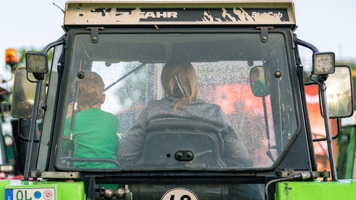 Eine Landwirtin und ihr kleiner Sohn in ihrem Trecker.