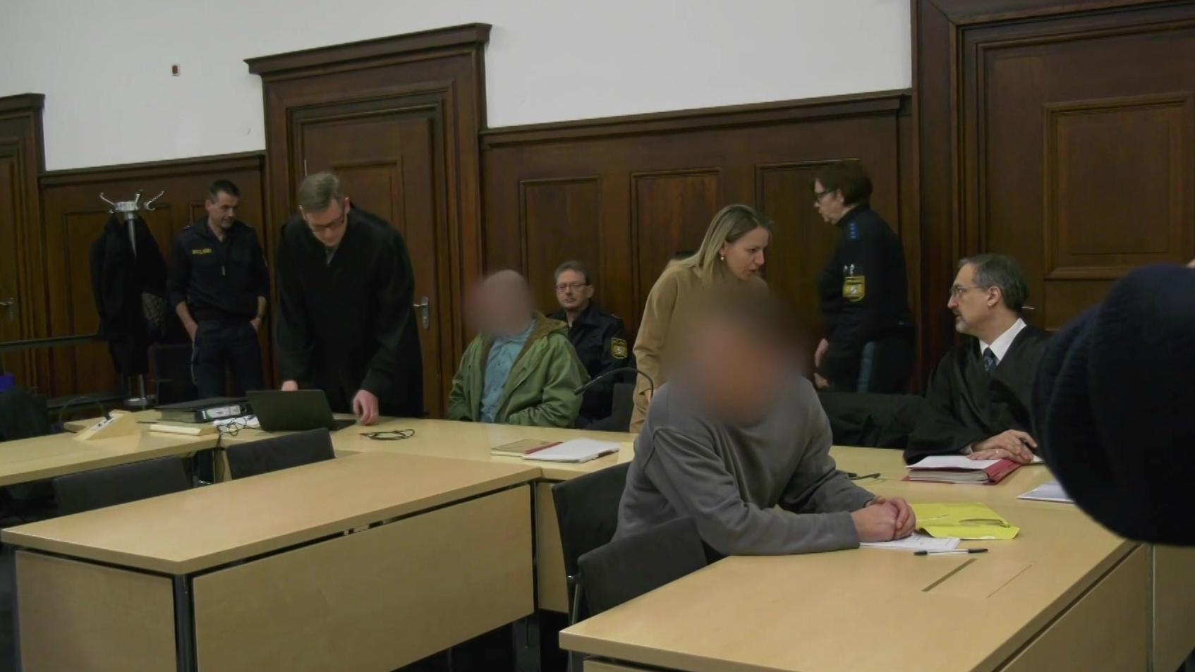Angeklagte und Polizisten im Gerichtssaal