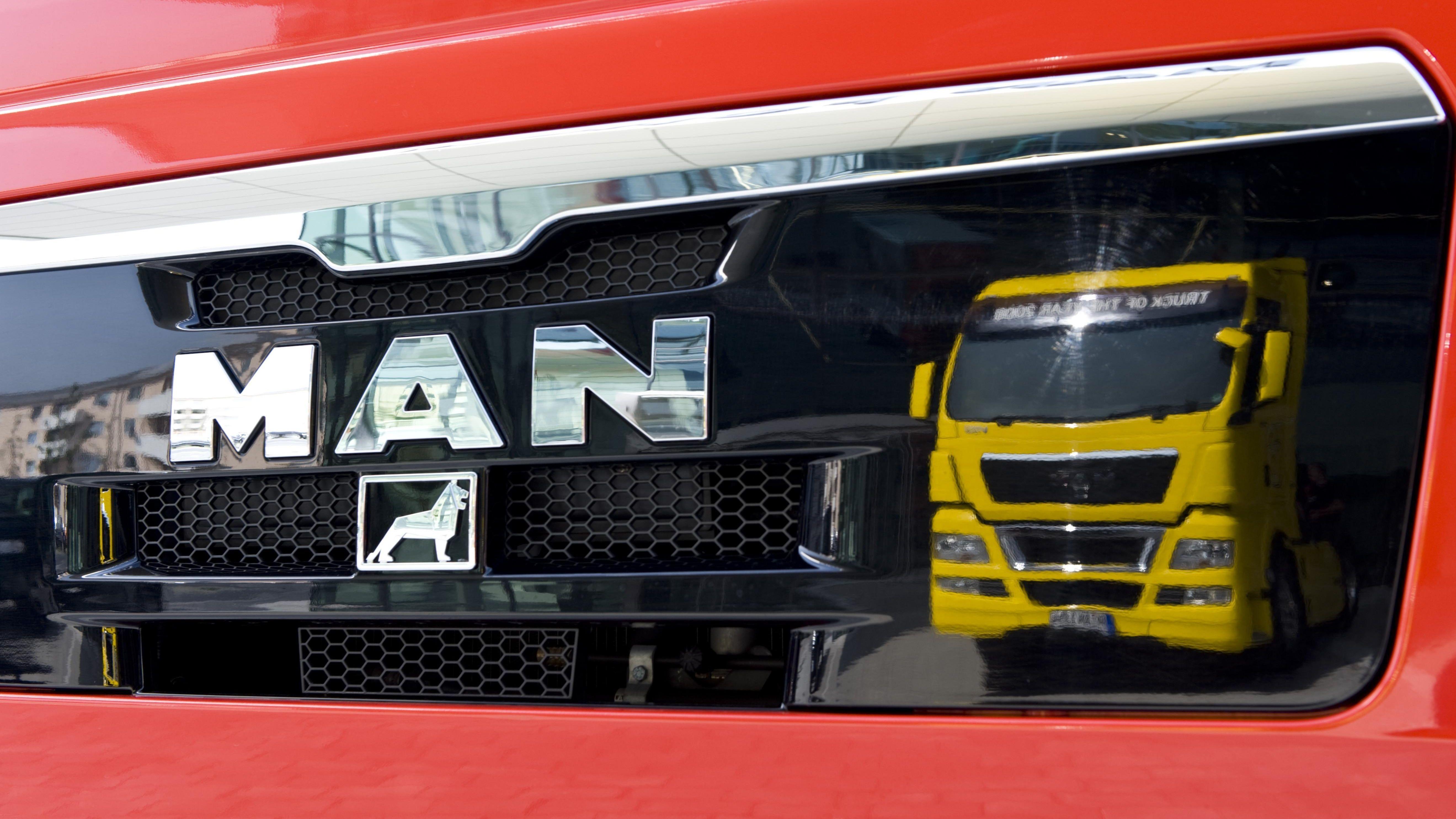 Ein gelber MAN Truck des Typs TGX 18.680 spiegelt sich in der Front eines anderen MAN Trucks.