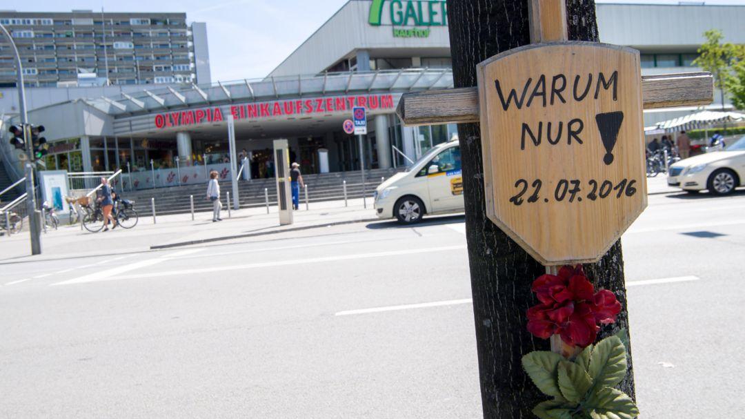 """Holzkreuz an einem Baum  vor dem OEZ mit der Aufschrift """"Warum nur"""""""