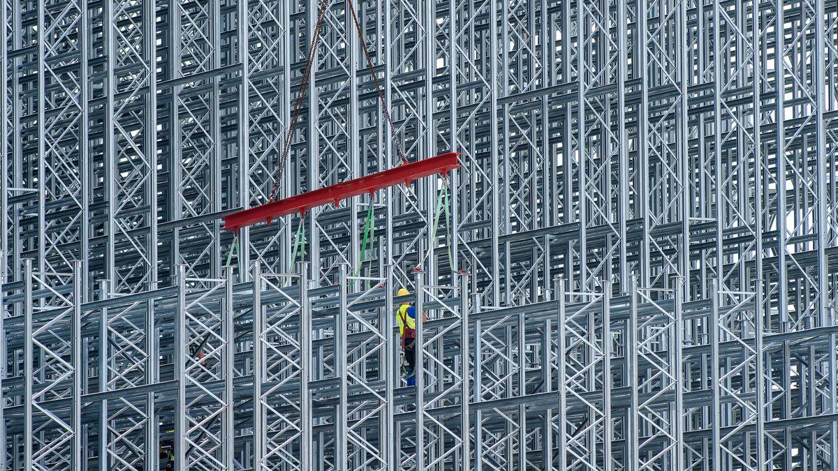 Arbeiter errichten das innere Gerüst eines Lagerhauses.