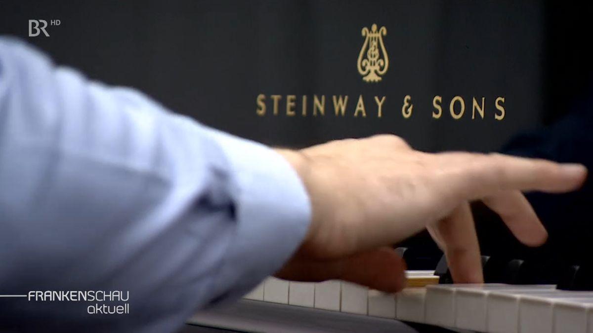 Finger drücken die Tasten eines Klaviers.