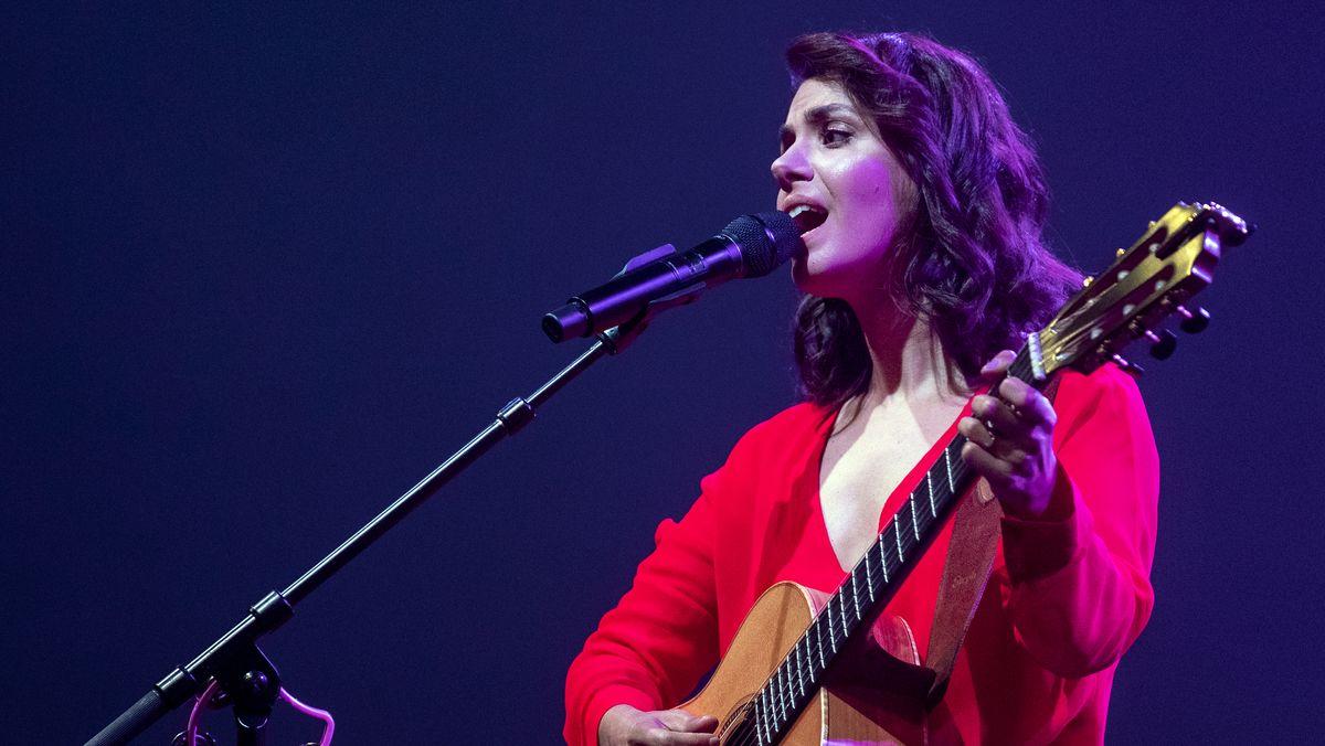 Katie Melua bei einem Auftritt singend, mit Akustik-Gitarre in der Hand in rotem Oberteil.